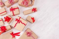 Christmas craft paper gifts with red ribbons closeup and bows on soft white wood table, top view, border. Christmas craft paper gifts with red ribbons closeup royalty free stock photo