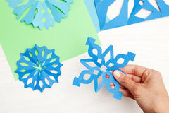 Christmas crafts. Paper snowflakes. Making Christmas decorations Royalty Free Stock Photography
