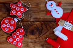 Christmas crafts to make at home. Felt star, Christmas tree, snowman and ball on a brown wooden background with copy space Stock Images