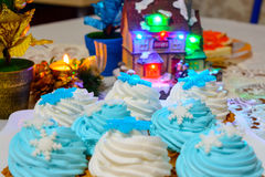 Christmas cream cakes and candles close up on the table with colored lights. Christmas cream cakes and candles close up on the festive table with colored lights Stock Photo