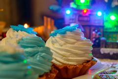 Christmas cream cakes and candles close up on the table with colored lights. Christmas cream cakes and candles close up on the festive table with colored lights Royalty Free Stock Image