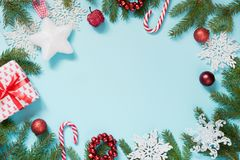 Christmas border with white and red decor, balls, gift, candy cane, snowflakes on blue. Flat lay. Top view. Copy space. Royalty Free Stock Photos