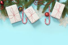 Christmas creative border with white and red decor, gifts, candy cane, snowflakes on blue background. Flat lay. Top view. Copy spa Royalty Free Stock Photos