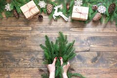 Christmas creative frame composition. Female hand holding spruce branch for making.  on the wooden background. Top view and copy space Royalty Free Stock Photography