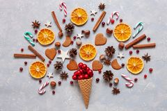 Christmas creativity concept with red balls, candy canes, cookies, spices, dry orange slices in the waffle. Flat lay, Close-up. Top view on light wooden table royalty free stock photography