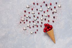Christmas creativity concept with red balls, cranberry, stars in the waffle cone sprinkled with red sugar. Flat lay, Close-up. Top view on light wooden table royalty free stock image