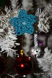 Christmas crochet star ornament. Christmas ornaments with a blue shinny crocheted star on top of a white tree Stock Images