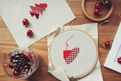 Christmas cross stitch designs and decorations on wooden table. Preparing handmade gifts for New Year and Christmas. At home Stock Image