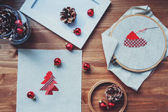 Christmas cross stitch designs and decorations on wooden table. Preparing handmade gifts for New Year and Christmas Stock Photos