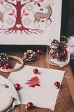 Christmas cross stitch designs and decorations on wooden table. Preparing handmade gifts for New Year and Christmas Stock Image