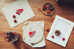 Christmas cross stitch designs and decorations on wooden table. Preparing handmade gifts for New Year and Christmas Royalty Free Stock Images