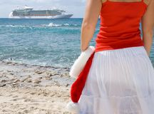 Christmas Cruise. Woman looking at cruise ship holding a Santa Hat. Theme shot for holiday travel Stock Images