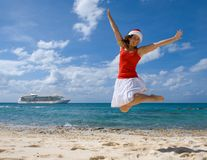 Christmas Cruise. Woman jumping for joy she is spending the holiday in the tropics. Cruise ship in the background. Theme shot for holiday travel Royalty Free Stock Images