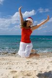Christmas Cruise. Woman jumping for joy as she is spending the holiday in the tropics. Theme shot for holiday travel Stock Images