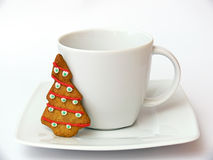 Christmas cup. The white cup with gingerbread - Christmas tree on the saucer. Isolated on the white background Stock Image