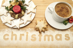Christmas Cup of Coffee with Cookies. Christmas cup of coffee with star cookies  on a plate and the word christmas written in flour Royalty Free Stock Photography