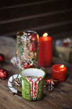 Christmas cup and decorations on wooden table. Christmas cup with coffee, red candles and decorations on wooden table Royalty Free Stock Images