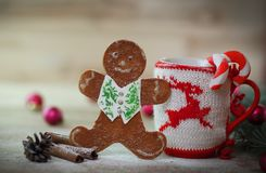 Christmas Cup ornament and a fun gingerbread on a wooden table royalty free stock photos