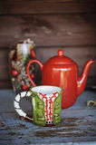 Christmas cup and red tea pot on wooden table. With decorations on background Stock Photos