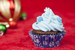 Christmas cupcake. Sweet christmas cupcake decorating with icing and sprinkles on a red background stock photos