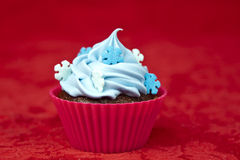 Christmas cupcake. Sweet christmas cupcake decorating with icing and sprinkles on a red background royalty free stock image