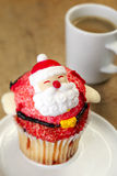 Christmas cupcake. Close-up of decorated christmas cupcake with coffee in background Stock Photo