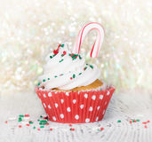 Christmas cupcake with candy cane. Christmas cupcake with a candy cane against sparkling holiday background stock photos