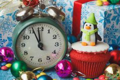 Christmas cupcake with colored decorations. Penguin made from confectionery mastic, soft focus background Royalty Free Stock Photography