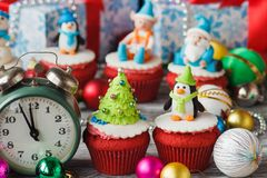 Christmas cupcakes with colored decorations, soft focus background. Christmas cupcake with colored decorations Christmas tree and penguin made from confectionery Stock Photos