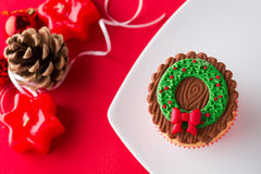 Christmas cupcake in decorative setting. Christmas cupcake on white plate in decorative setting stock photos