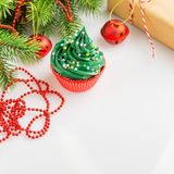 Christmas cupcake in red cup with festive decorations on white b. Christmas green cupcake with colorful sprinkles in red cup on white background with festive royalty free stock images