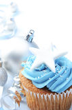 Christmas cupcake with silver ornaments. Blue icing frosted cup cake with silver christmas ornaments and decorations, plenty of copyspace Stock Image