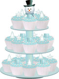 Christmas cupcake stand. Christmas cupcakes with presents, stars and Christmas trees on a blue stand Royalty Free Stock Images