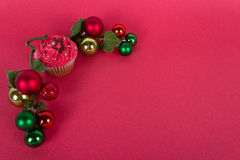 Christmas cupcake and tree ornaments on red background Royalty Free Stock Images