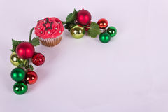 Christmas cupcake and tree ornaments on white background Royalty Free Stock Photos