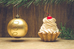 Christmas cupcake on wooden background with fir frame with golden ball. Christmas cupcake on wooden background with golden ball Royalty Free Stock Images