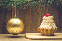 Christmas cupcake on wooden background with golden ball. Cherry cake on a wooden support with a Christmas tree decoration Stock Photography
