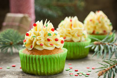 Christmas cupcakes with buttercream frosting and sugar confetti. Dessert cake with cream and red green sprinkle. Christmas and New Year holiday food stock image
