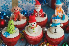 Christmas cupcakes with colored decorations. Made from confectionery mastic, soft focus background Royalty Free Stock Images