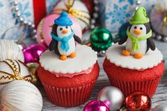 Christmas cupcakes with colored decorations. Penguins made from confectionery mastic, soft focus background Royalty Free Stock Photography