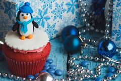 Christmas cupcakes with colored decorations. Christmas cupcake with colored decorations, Penguin made from confectionery mastic, soft focus background Stock Image