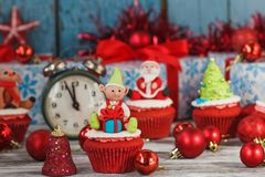 Christmas cupcakes with colored decorations, soft focus background. Christmas cupcakes with colored decorations Elf made from confectionery mastic, soft focus Stock Photos