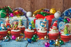 Christmas cupcakes with colored decorations made from confection. Ery mastic, soft focus background Royalty Free Stock Images