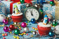 Christmas cupcakes with colored decorations penguin made from confectionery mastic. Soft focus background Stock Photo