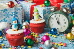 Christmas cupcakes with colored decorations penguins made from confectionery mastic. Soft focus background Royalty Free Stock Image