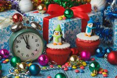 Christmas cupcakes with colored decorations penguins made from confectionery mastic. Soft focus background Stock Photo