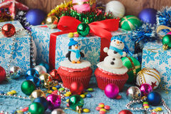 Christmas cupcakes with colored decorative snowman and penguin made from confectionery mastic. Soft focus background Stock Photo