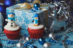 Christmas cupcakes with colored decorative snowman and penguin made from confectionery mastic. Soft focus background Royalty Free Stock Photo