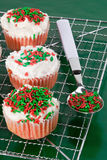 Cupcakes. Christmas cupcakes cooling off on a kitchen rack. A spoon filled with holiday colored sprinkles Stock Photos