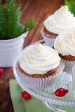 Christmas cupcakes with cream cheese frosting. Homemade christmas cupcakes with cream cheese frosting on cake stand on wooden background with spruce twigs in royalty free stock photo